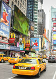 Times Square, New York City. On the island of Manhattten in the United States of America. Busy street with iconic yellow taxi cabs and neon signs of the theatre royalty free stock images