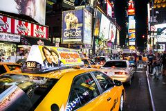 Times Square, New York City, New York, United States - circa 2012 taxi cabs driving at night with brightly lit advertising signs. Taxi cabs driving times square royalty free stock images