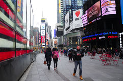 Times Square New York City. Pedestrians walking through Times Square in Manhattan during a cloudy spring day in New York City stock images