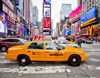 Times Square. NEW YORK - DECEMBER 17: Yellow cab speeds through Times Square the busy tourist intersection of neon art and commerce and is an iconic street of royalty free stock image