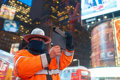 Times Square. NEW YORK, NY - MARCH 14, 2016: a public safety officer taking photo in Times Square. Times Square is a major commercial intersection and Stock Photography