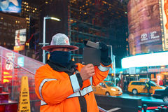 Times Square. NEW YORK, NY - MARCH 14, 2016: a public safety officer taking photo in Times Square. Times Square is a major commercial intersection and Royalty Free Stock Photos