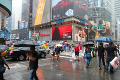 Times Square. NEW YORK, USA - JUNE 10, 2013: People walk in rain in Times Square, New York City. Times Square has over 39 million annual visitors. It is an royalty free stock photo