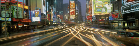 Times Square at night. This is Times Square at night. There are streaked lights from the cars traveling through the square. There are neon lights from the royalty free stock image