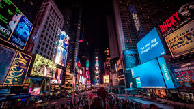 Times Square at Night. The bright lights of Times Square, New York City at night. The buildings are covered in flashing signs and lights. A wide view following stock photo