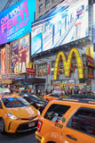 Times Square przedstawienia billboardy z ludźmi, żółty taxi ruch drogowy przy nocą w Nowy Jork Zdjęcia Royalty Free
