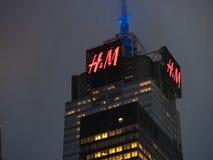 4 Times Square que construyen con la muestra de H&M que asoma arriba en una d lluviosa imagen de archivo