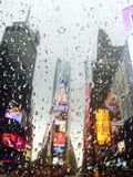 Times Square rain. Rain droplets on taxi window while driving through Times Square in NYC Royalty Free Stock Images