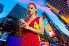 Times Square rojo NYC de la charla del teléfono del vestido de la muchacha rubia Fotos de archivo libres de regalías