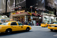 Times Square Traffic. Yellow cabs and the subway are the main modes of transportation in midtown New York with a NYPD security camera installed at the corner Royalty Free Stock Photo