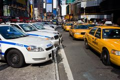 Times Square Vehicles. A typical vision on the streets if New York City; A line up of Police cars and Taxi Cabs driving on Broadway through Times Square royalty free stock photography