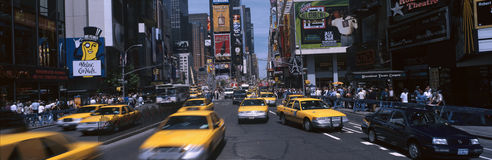 Times Square with yellow taxis during the day. This is Times Square during the day. There are yellow taxis and oncoming traffic amidst the billboards and signs royalty free stock photography
