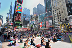 Times Square Yoga. Hundreds of people participate in a yoga event in Times Square New York City. Skyscrapers and billboards surround yogis as they warm up stock photography