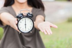 Times to pay the money bill or tax now, It`s time to give me something concept. Asian women hand open palm and hold retro clock at 6 o`clock Royalty Free Stock Photo
