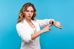 Free Times Up! Portrait Of Serious Woman Pointing At Watch On Hand And Looking Disapprovingly. Blue Background Royalty Free Stock Image - 171861116