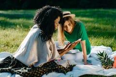 Timespending 2 жизнерадостных молодых привлекательных подруг Прелестная африканская девушка показывает что-то смешное на ей Стоковая Фотография RF