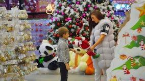 Timespending da mãe e de seu filho pequeno na alameda durante feriados do Natal O menino está trazendo dois Santa vídeos de arquivo