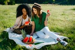 Timespending de deux amie multi-ethniques La fille assez africaine cause par l'intermédiaire du mobile et mange la pastèque Photographie stock libre de droits