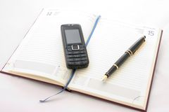 Timetable. A opened timetable with a pen with a gilded clip and cellphone on it Royalty Free Stock Photo