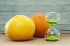 Timglas med apelsinen och grapefrukten på en träbakgrund, närbild arkivbilder