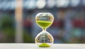 Timglas med grön sand på en suddig bakgrund fotografering för bildbyråer