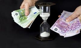 Timglas och pappers- pengar Tid är pengarbegreppet arkivbild
