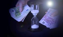 Timglas och pappers- pengar Tid är pengarbegreppet fotografering för bildbyråer