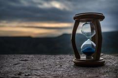 Timglasbortgång av moln för Tid schackningsperiod Ett timglas av en ljus blå himmel med pösig vit fördunklar framme bortgång för  Royaltyfria Bilder