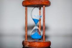 Timglascloseup som reflekterar och avspeglas på den glass tabellen med färgrik blå bakgrund Arkivfoton