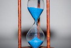 Timglascloseup som reflekterar och avspeglas på den glass tabellen med färgrik blå bakgrund Fotografering för Bildbyråer