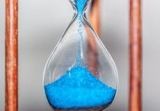 Timglascloseup som reflekterar och avspeglas på den glass tabellen med färgrik blå bakgrund Royaltyfria Bilder