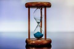 Timglascloseup som reflekterar och avspeglas på den glass tabellen med färgrik blå bakgrund Arkivbild