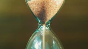 Timglaset på en träbakgrund, sanden faller inom stock video