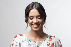 Timid gorgeous girl with bun hairstyle smiling and looking down Royalty Free Stock Photos