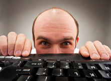 Timid nerd hiding under computer keyboard Stock Photo