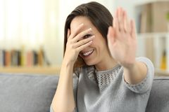 Timid woman hiding face at home. Timid woman hiding face with the hand sitting on a couch in the living room at home Royalty Free Stock Photo