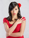 Timid Young Woman. Beautiful young Asian woman with red flower in hair Stock Images