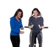 Timing. Young caucasian woman trainning in the gym with personal trainer woman Royalty Free Stock Image