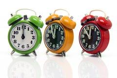 Timing alarm clocks. Timing red yellow and green alarm clock untill twelve oclock closeup with nice reflection royalty free stock photos