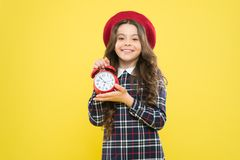 Timing is everything. Happy small child showing proper timing on yellow background. Little girl smiling and holding. Alarm clock with timing signal. Her timing royalty free stock photo