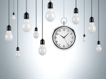 Timing and new ideas. Several bulbs hanging from th ceiling, one pocket watch among them. Grey background. Concept of time and new ideas Royalty Free Stock Image