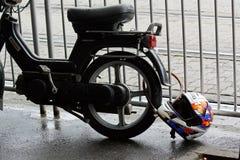 TIMISOARA, κράνος ποδηλατών της ΡΟΥΜΑΝΙΑΣ â€ «cca 2012 που δένεται σε μια ρόδα μοτοσικλετών με μια αλυσίδα σε μια υγρή οδό στοκ φωτογραφία με δικαίωμα ελεύθερης χρήσης
