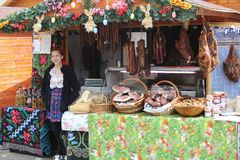 TIMISOARA, РУМЫНИЯ 04 04 2017 усмехаясь девушка магазина в традиционном костюме продает традиционные продукты свинины как сосиски стоковое фото