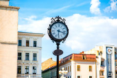 Timisoara. Beautiful vintage clocks on Victory square with Opera house on background in Timisoara city on suset, Romania Stock Images