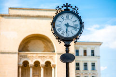 Timisoara. Beautiful vintage clocks on Victory square with Opera house on background in Timisoara city on suset, Romania Royalty Free Stock Photos