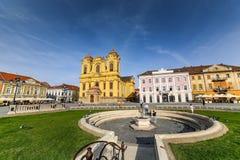 Timisoara - den katolska kupolen i Piata Unirii Union Square med att förbigå för folk Arkivbild
