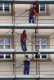 TIMISOARA, ROEMENIË-02 15 2010 Drie bouwvakkers die beschermend toestel in rood dragen en blauw, het werk aangaande steiger op fl royalty-vrije stock foto