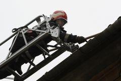 TIMISOARA, ROEMENIË-12 08 2010 maakt een brandweerman die het specifieke materiaal met rode helm dragen de rand van een dak schoo stock afbeeldingen