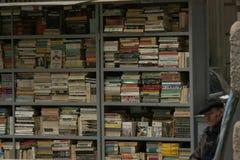 TIMISOARA, ROMÊNIA 05 07 2018 um vendedor de livro de segunda mão idoso situado na frente de seu suporte de livros usados em uma  fotos de stock royalty free