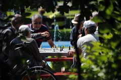 TIMISOARA, ROMANIA – 06.05.2014 Group of elderly people play chess in a park. stock photo